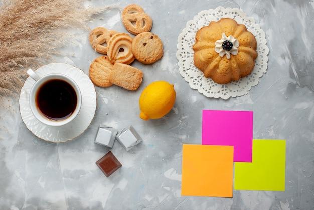 Вид сверху на чашку горячего чая с шоколадным лимонным пирогом и печеньем на свете, сладкое печенье, конфеты, шоколад, чай, печенье Бесплатные Фотографии