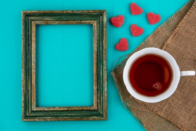 コピースペースと青色の背景にマーメラドと荒布とフレームにお茶のカップのトップビュー 無料写真