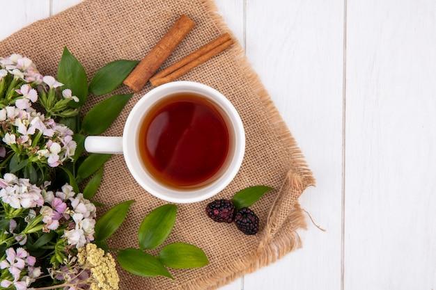 Вид сверху на чашку чая с корицей и цветами на бежевой салфетке на белой поверхности Бесплатные Фотографии