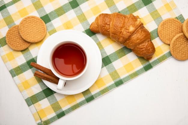 コピースペースと白い背景の布にティーバッグにシナモンとお茶のカップと日本のバターとクッキーのトップビュー 無料写真