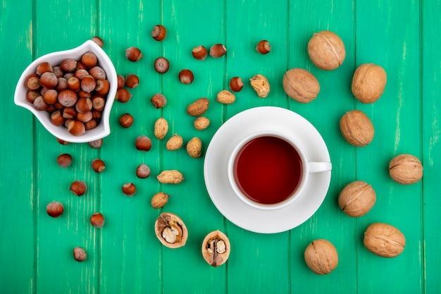 Вид сверху на чашку чая с фундуком в миске грецкими орехами и арахисом на зеленой поверхности Бесплатные Фотографии