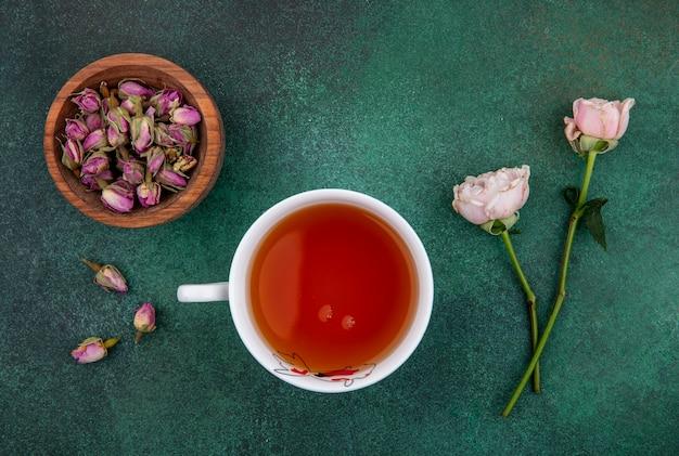 緑の表面に光のピンクのバラとボウルに乾燥したバラのつぼみのお茶のトップビュー 無料写真