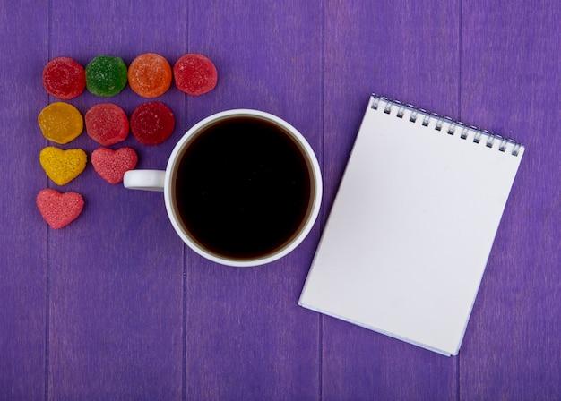 Вид сверху чашки чая с мармеладом и блокнотом на фиолетовом фоне Бесплатные Фотографии