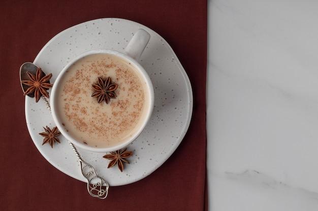 Вид сверху на чашку с индийским чаем масала и специями на мраморном столе, место для текста Premium Фотографии