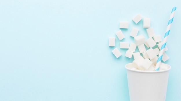 Вид сверху на чашку с кубиками сахара и соломинкой Premium Фотографии
