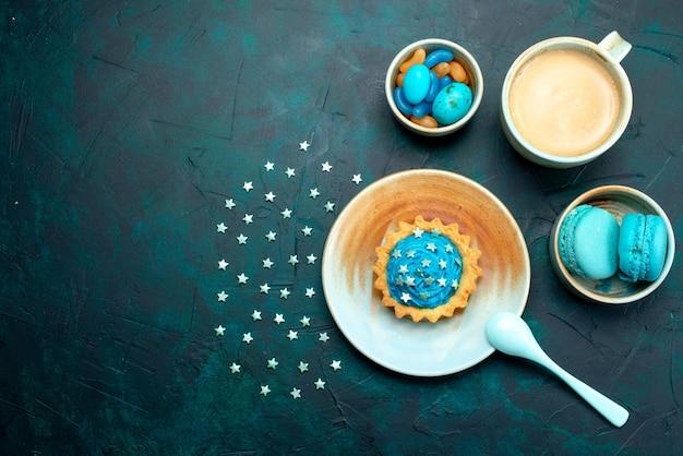 一杯のコーヒーとマカロンの横にある星とブルーチョコレートのカップケーキの上面図 無料写真