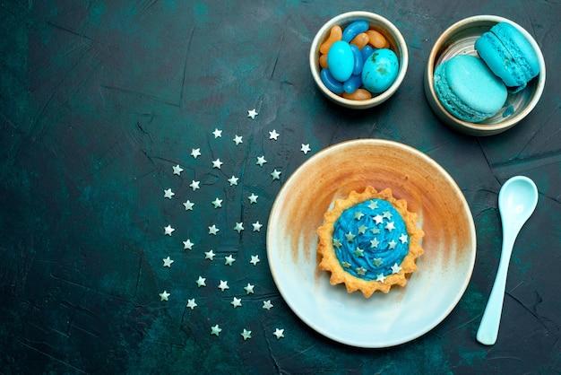 マカロンとお菓子のプレートの横に星の装飾が施されたカップケーキの上面図 無料写真