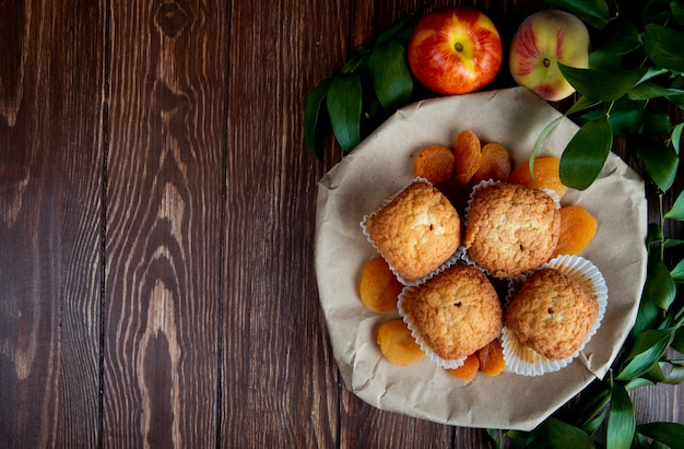 コピースペースを持つ葉で飾られた木の板にドライプラムと桃のカップケーキの平面図 無料写真