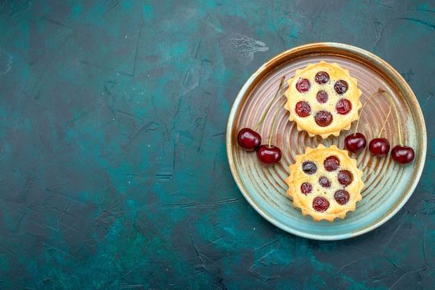Вид сверху кексов с вкусной вишней на темно-синем, Бесплатные Фотографии