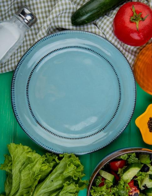 緑のレタスキュウリバジルトマトと塩黒コショウと空のプレートとしてカットと全体の野菜のトップビュー 無料写真