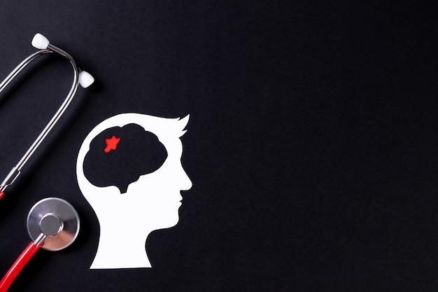 Взгляд сверху отрезанного бумажного мозга с стетоскопом. всемирный день опухолей головного мозга. Premium Фотографии