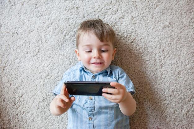 画面電話を押しながらスマートフォンで自分に写真を撮るかわいい男の子の平面図です。 Premium写真