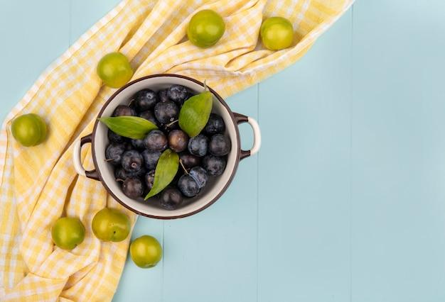 복사 공간이 파란색 배경에 노란색 체크 식탁보에 고립 된 녹색 체리 자두 그릇에 어두운 보라색 Sloes의 상위 뷰 무료 사진