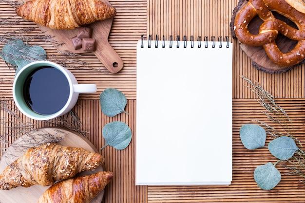 Вид сверху вкусного завтрака с кофе и выпечкой, с тетрадью в центре Premium Фотографии
