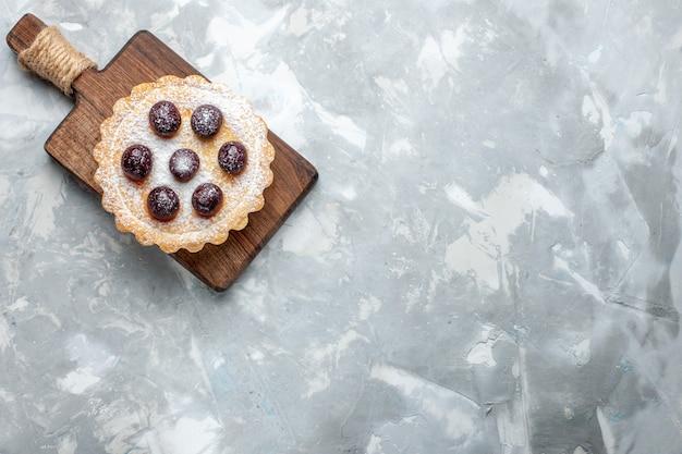 Вид сверху вкусного торта с вишней на светлом столе, пирожного, сладкого сахарного печенья Бесплатные Фотографии
