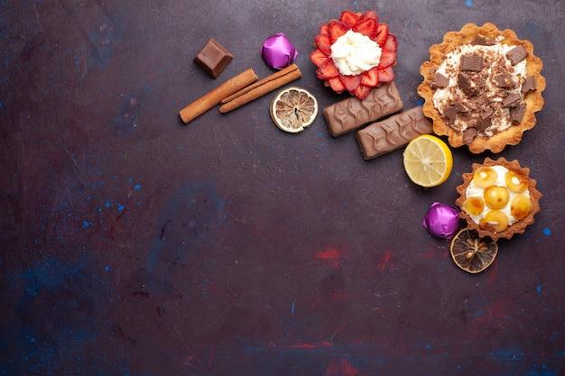 Вид сверху вкусных тортов вместе с корицей и конфетами на темной поверхности Бесплатные Фотографии