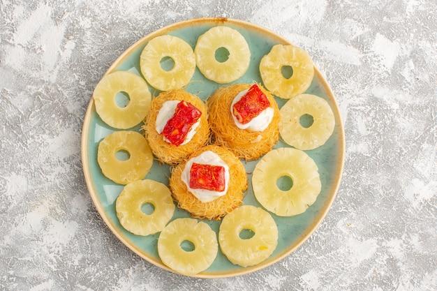 Вид сверху вкусных тортов с белым кремом и красным мармеладом внутри тарелки на светлой поверхности Бесплатные Фотографии