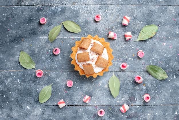 おいしいクリーミーなケーキとグレーのスライスしたキャンディー、ケーキの甘い焼き砂糖の上面図 無料写真