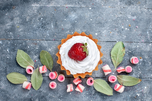 Вид сверху вкусного сливочного торта со свежей клубникой и нарезанными розовыми конфетами на сером, сладкий торт, выпечка, крем, мармелад Бесплатные Фотографии