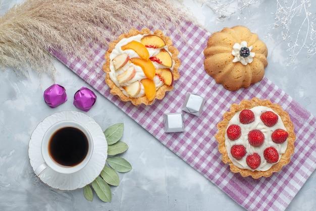 Вид сверху вкусных кремовых пирожных с нарезанными фруктами вместе с шоколадными конфетами и чаем на светлом полу торт бисквит сладкий крем испечь чай сахар Бесплатные Фотографии