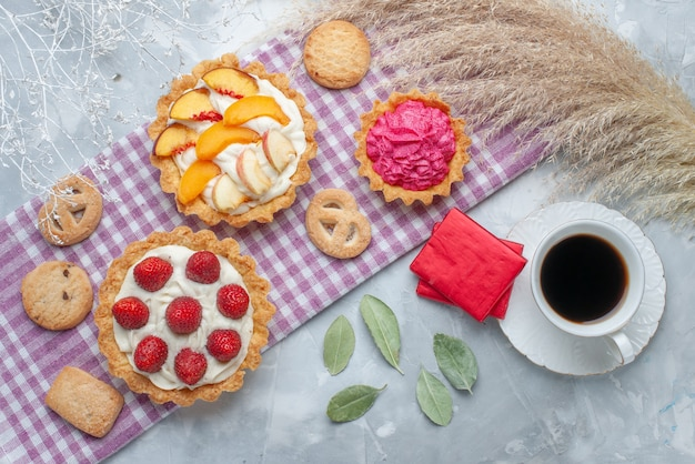 ライトデスクでクッキーとお茶と一緒にスライスしたフルーツとおいしいクリーミーなケーキの上面図、ケーキビスケットの甘いクリーム焼き 無料写真