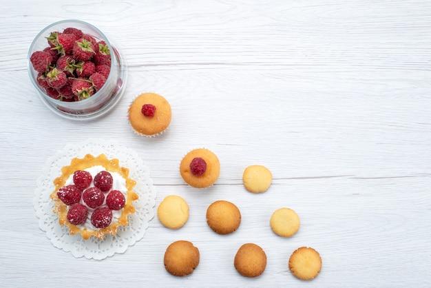 ラズベリーとイチゴとクッキーの光の上のおいしい小さなケーキ、ケーキビスケットスイートベリーの上面図 無料写真