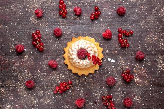Вид сверху на вкусный маленький торт с сахарной пудрой и малиной, клюквой, коричневым, ягодным, фруктовым бисквитом Бесплатные Фотографии