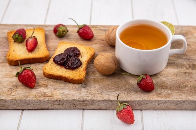 白い木製の背景に木製キッチンボードにライムと紅茶のカップとパンにおいしいイチゴのトップビュー 無料写真