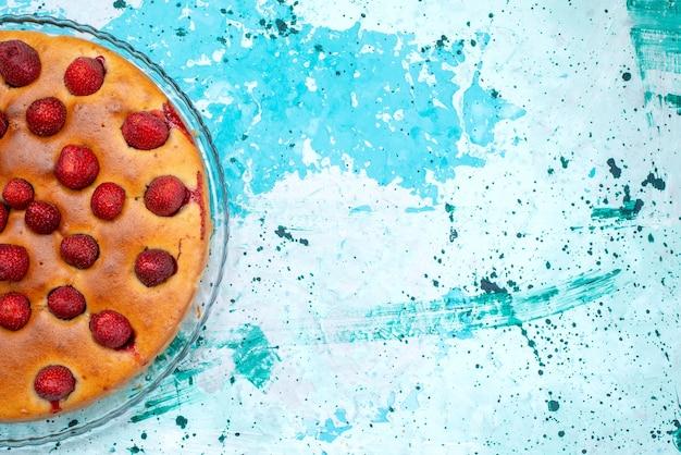 Вид сверху вкусного клубничного торта круглой формы с фруктами сверху на ярко-синем тесте для торта, сладком бисквитном сахаре, фруктовой ягоде Бесплатные Фотографии
