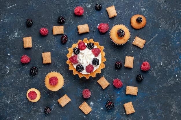 Вид сверху на вкусный сладкий торт с печеньем из разных ягод и вкусным кремом на темно-сером, ягодном цвете бисквитного торта Бесплатные Фотографии
