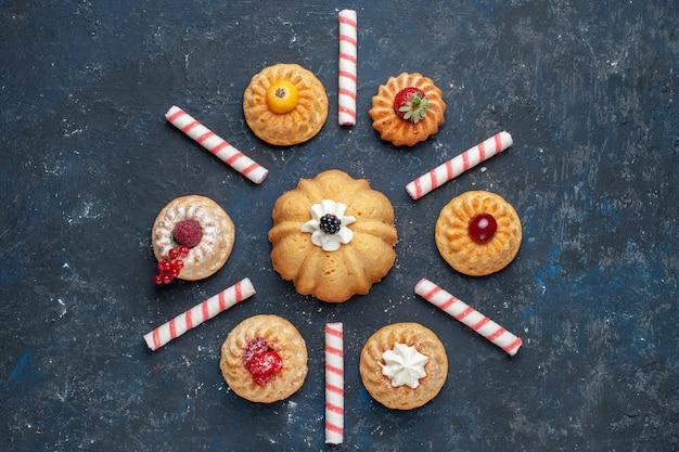 Вид сверху на разные вкусные торты со сливками и ягодами вместе с розовыми конфетами на темных, ягодных фруктовых тортах, бисквитном сладком Бесплатные Фотографии