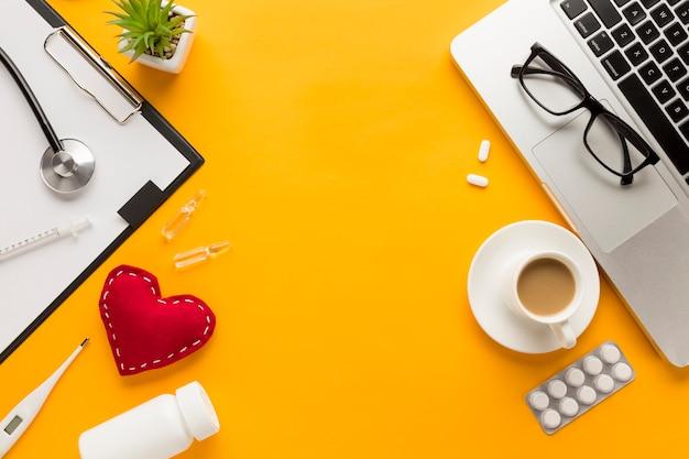 コーヒーカップと医師のデスクの平面図。黄色の背景のラップトップ 無料写真