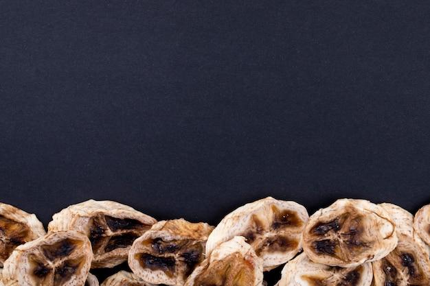 コピースペースと黒の背景の下部に配置された乾燥バナナチップのトップビュー 無料写真