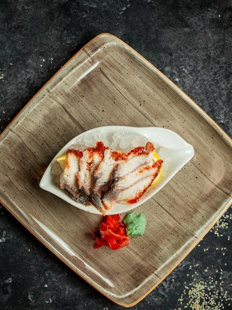 氷とレモンの上に添えたウナギのソースの平面図 無料写真