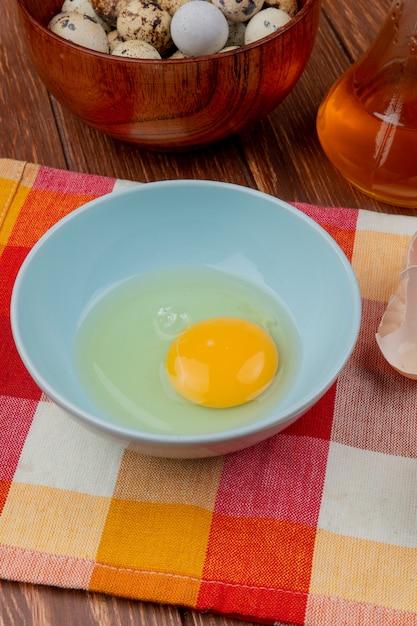 木製の背景にリンゴ酢とチェックのテーブルクロスの上の青いボウルに卵の白と卵黄の平面図 無料写真