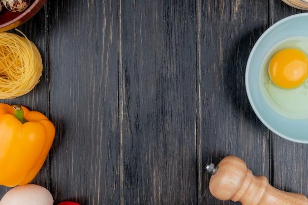 コピースペースを持つ木製の背景にオレンジ色のピーマンとボウルに卵黄と白のトップビュー 無料写真