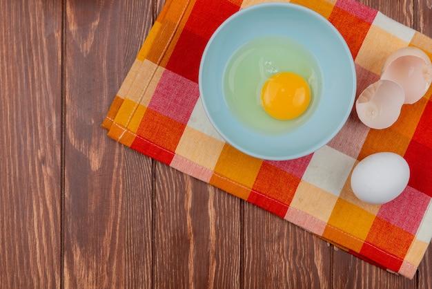 コピースペースを持つ木製の背景にチェックされた布の上のひびの入った卵の殻と白いボウルに卵黄と白の平面図 無料写真