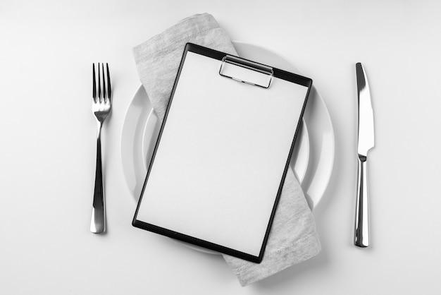 Вид сверху пустого меню на тарелке со столовыми приборами Бесплатные Фотографии