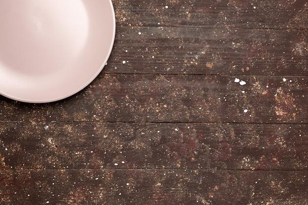 茶色の素朴なプレートフードキッチンウッドにピンク色の空のプレートの上面図 無料写真