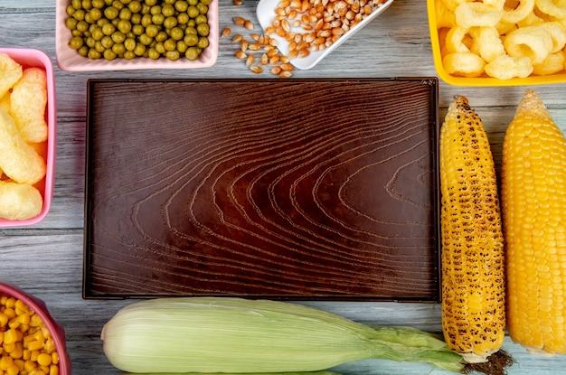 나무 표면에 녹색 완두콩 옥수수 씨앗 옥수수 팝 곡물과 옥수수 속 빈 트레이의 상위 뷰 무료 사진