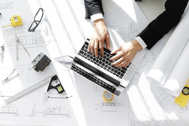 노트북을 사용하여 건설 프로젝트에서 작업하는 공식적인 양복을 입고 엔지니어의 상위 뷰 무료 사진