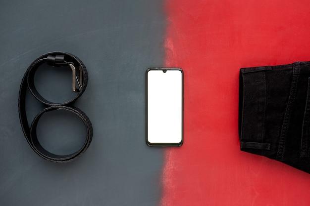 Вид сверху модного черного кожаного ремня, черных джинсов и телефона на серой и красной поверхности Premium Фотографии