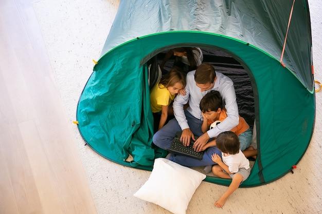 Вид сверху отца, сидящего с милыми детьми в палатке дома и с помощью портативного компьютера. прекрасные дети смотрят фильм с отцом, веселятся и расслабляются. детство, семейное время и концепция выходных Бесплатные Фотографии