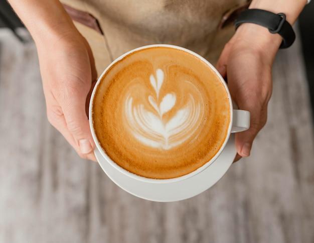 装飾された一杯のコーヒーを手に持って女性バリスタの上面図 無料写真