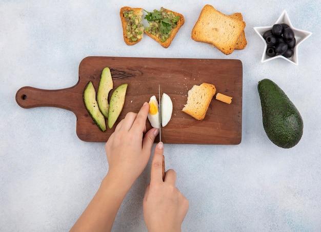 Вид сверху женской руки, разрезающей вареное яйцо на кусочки на деревянной кухонной доске с ломтиками авокадо, поджаренным ломтиком хлеба с черными оливками на белом Бесплатные Фотографии