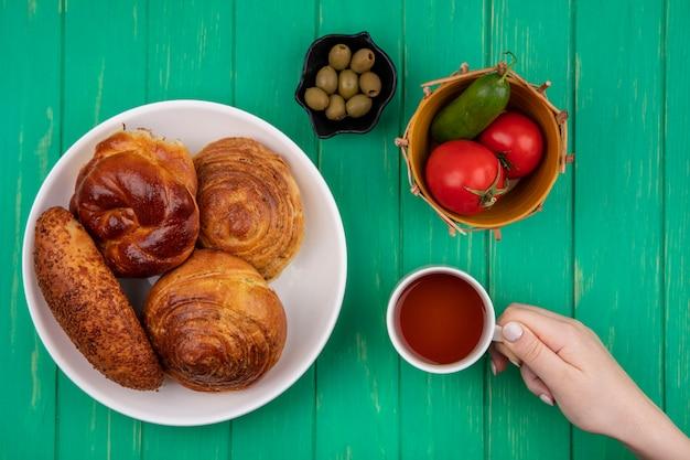 緑の背景の上のバケツにトマトとキュウリとトマトとキュウリの黒いボウルにオリーブとオリーブと白いプレートにパンとお茶のカップを持っている女性の手の上面図 無料写真
