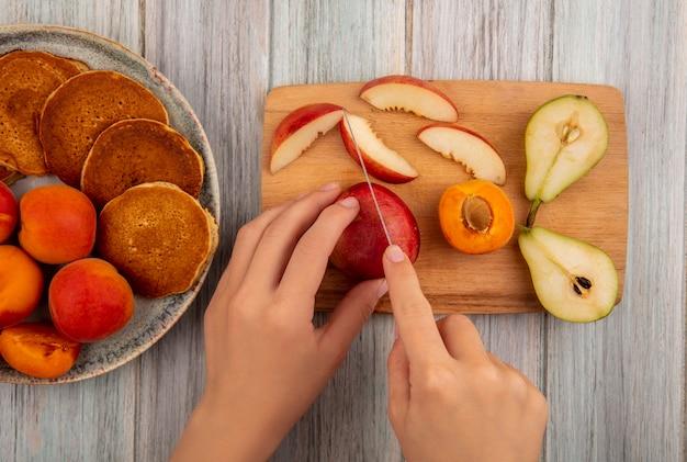ナイフで桃を切る女性の手の平面図とスライスされた桃はまな板と木製の背景にアプリコットとパンケーキのプレートに梨をカット 無料写真