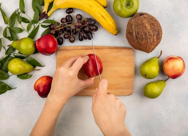 まな板の上にナイフで桃を切る女性の手と白い背景の上の葉を持つブドウ梨ココナッツバナナりんごの平面図 無料写真