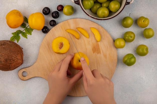 白い背景で隔離の桃とココナッツとナイフで木製キッチンボードに黄色の桃を切る女性の手の上から見る 無料写真
