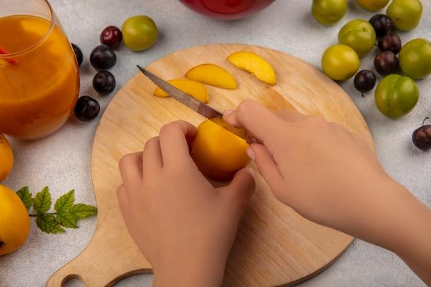 白い背景に分離された緑のチェリープラムと桃とナイフで木製キッチンボードに黄色の桃を切る女性の手の上から見る 無料写真